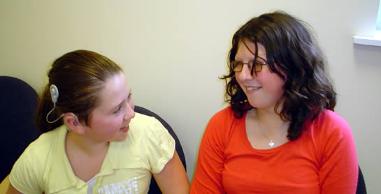 Girl with cochlear implant speaking to another girl