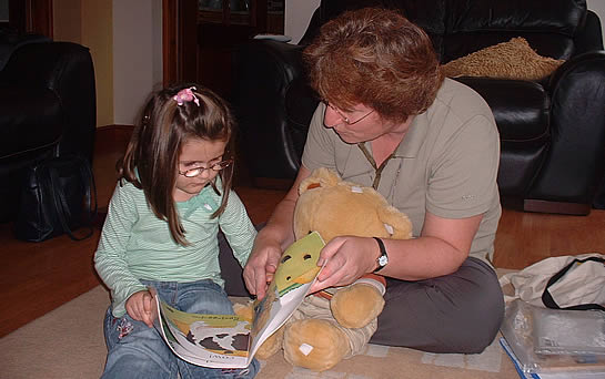 Young girl with older woman reading at home